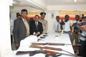 Public Security Minister, Khemraj Ramjattan; Prime Minister Moses Nagamootoo and Police Commissioner Seelall Persaud viewing a number of illegal firearms that had been surrendered during a gun amnesty last year.