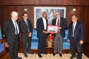 "President David Granger receives a copy of the book ""Hand-in-Hand History of Cricket in Guyana 1865-1897"" from the insurance company's board member Mr. John Carpenter"