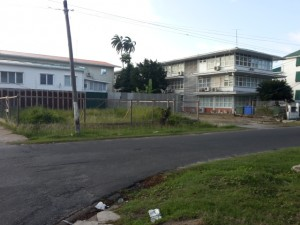 The two plots of land at the corner of Middle and Carmichael Streets. In the background at right is the building housing the Attorney General Chambers and Ministry of Legal Affairs.