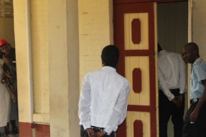 """Donald """"Short man"""" Trapp and Kemo """"Trini"""" Corbin exiting the prisoners' chute at the Georgetown Magistrates' Court to avoid their faces being photographed."""
