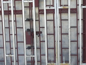 THE LOCKED DOOR of GA Shortt Imports following an armed robbery nearby. The owner was shot by one of the bandits.