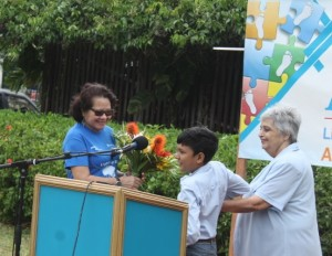 First Lady, Sandra Granger received a bouquet from a student of the Step by Step Foundation. At right is the foundation's Director Dr. Suraiya Ismail.