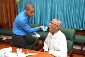 President David Granger allows the painless removal of the sample for his Ancestry DNA test by Mr. Shawn Manbodh, Quality Manager and Medical Technologist, which was done at State House Monday morning