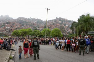 Venezuelan soldiers outside a supermarket while people lining up to buy basic food items in Caracas, Venezuela, on Sunday.