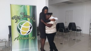 A Fly Jamaica representative comforts Lovern Williams-Oliver. The airline presented her with a free return ticket so that she can attend the funeral of her daughter, Shemel Mercurius, who was shot dead on May 31, 2016 while babysitting a three-year old cousin.