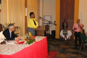 Junior Vice President of the Georgetown Chamber of Commerce and Industry, Nicholas Boyer (standing and holding microphone) asks Minister of Business, Dominic Gaskin (seated at table) a question.
