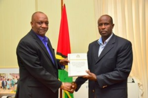 Minister of State, Joseph Harmon earlier this month receiving the Commission of Inquiry Report into allegations against CANU by self-confessed drug lord Barry Dataram.