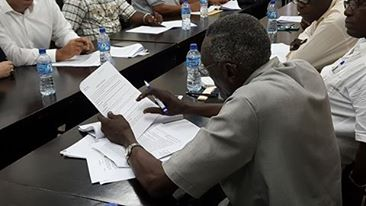 Consultant to the Labour Department of the Ministry of Social Protection reading a copy of the Contract for Service.