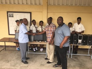 Left to Right: Old Boy of Tutorial High School, Malcolm Parris hands over the computers to Deputy Headteacher, Gerald Miller in the presence of Information Technology Teacher, Gerald Miller and students of Tutorial High School.