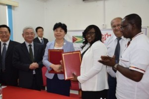 Minister within the Ministry of Public Health Dr. Karen Cummings and Vice Minister of National Health and Family Planning Commission of the People's Republic of China exchange the signed certificates that covered the gifts that had been handed over