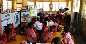 A Digicel staff member joins students of St. Cuthbert's Mission Nursery School in reading on International Literacy Day 2016.