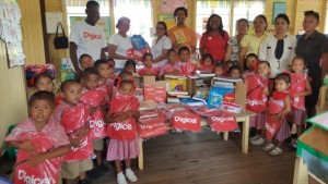 Digicel staff members with teachers and students of St. Cuthbert's Mission after they were presented with books and items by the company in observance of International Literacy Day 2016.