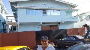 "Lawrence ""Larry"" Singh standing in front of the bond on 29 Sussex Street, Albouystown that he is renting government."