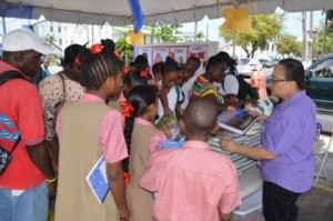 Students browsing the free books that were available at the literacy tent (GINA photo)