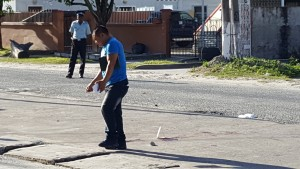 A detective walks past a tagged spot of blood where the shooting occurred outside Rio Night Club, Forshaw and Oronoque Streets, Queenstown, Georgetown.
