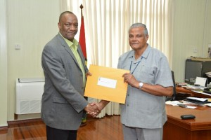 Minister of Sate, Mr. Joseph Harmon handing over the Terms of Reference (TOR) to Major General Ret'd Joe Singh, MMS for the investigations into the allegations of corruption and misconduct made by Mr. Kenwin Charles against members of the Guyana National Broadcasting Association (GNBA) Board.