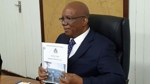 Minister of Finance, Winston Jordan showing off a copy of the Public Debt Management Report