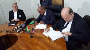 Left to Right: Commissioner- General of the Guyana Revenue Authority, Godfrey Statia looks on as Finance Minister, Winston Jordan and American Ambassador to Guyana, Perry Holloway sign the FATCA agreement.