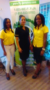A Fly Jamaica flight attendant flanked by two ticketing agents.