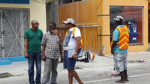 Kamau Cush (green T-shirt) and workers who were marking parking spaces on Main Street.