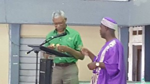 PNCR Leader, David Granger looking at a pin that his party's Region Three Chairman, Mark Walkes (right) presented him.