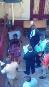 Mark Anthony in a stretcher in the Georgetown Magistrates Court yard while the charges were being read to him by Magistrate Delon Bess, as his lawyer and other officers of the court looked on.