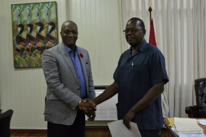 Minister of State, Joseph Harmon (left) and Retired Assistant Commissioner, Winston Cosbert.
