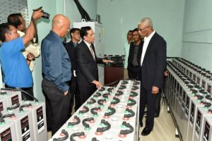 President David Granger takes a look at some of the batteries, which are a part of the solar electricity system at Demerara Bank Limited, as CEO, Mr. Pravinchandra Dave explains how the system works.