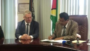 EU Ambassador Jernej Videtic looks on as Public Security Minister, Khemraj Ramjattan signs the EU Seaport Cooperation (SEACOP) Programme agreement.