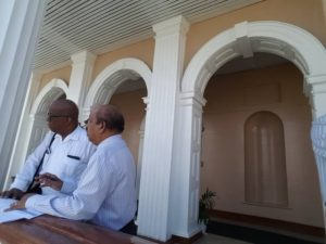 Finance Minister, Winston Jordan and Governor of the Bank of Guyana, Dr. Gobind Ganga speaking on the balcony of Parliament Building.